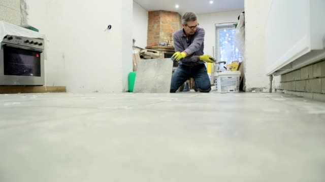 Construction worker puts ceramic tiles on the floor.