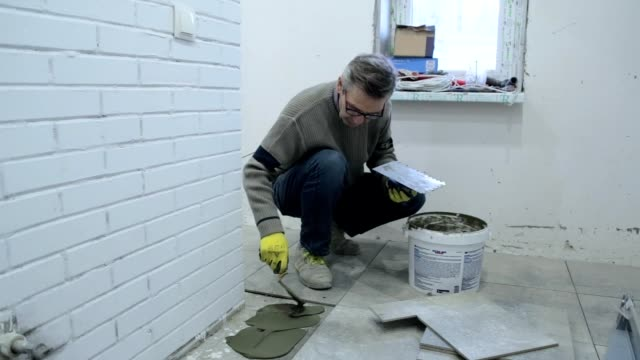 Construction worker puts the building glue on the floor.