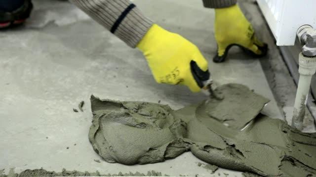 Bauarbeiter stellt die Gebäude-Kleber auf dem Boden.