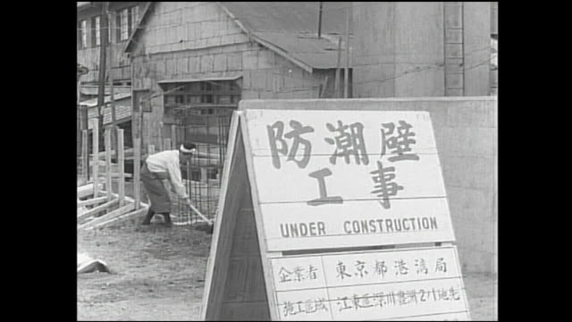 a construction worker rakes the ground behind a japanese sign at a flood control project. - 災害対策点の映像素材/bロール