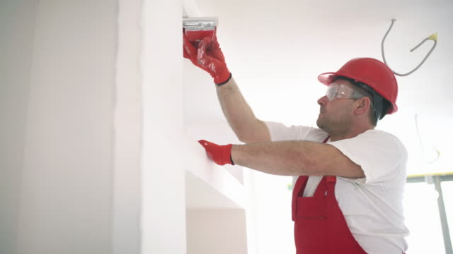 construction worker sanding a drywall. - professional painter stock videos and b-roll footage