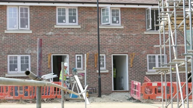 construction worker saws a length of wooden skirting board for a new home under construction at a crest nicholson holdings plc residential housing... - tape measure video stock e b–roll