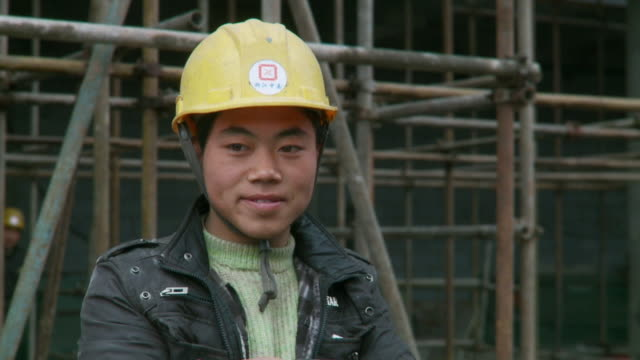 vídeos de stock e filmes b-roll de cu construction worker smiling / beijing, china - asiático e indiano