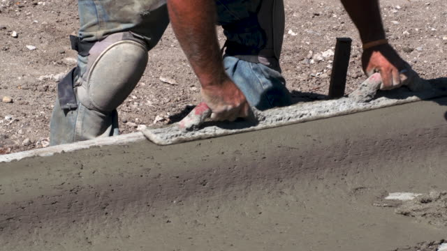 construction worker smoothing concrete - lavoratore emigrante video stock e b–roll
