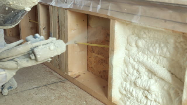 construction worker spraying expandable foam insulation between wall studs - spraying stock videos and b-roll footage