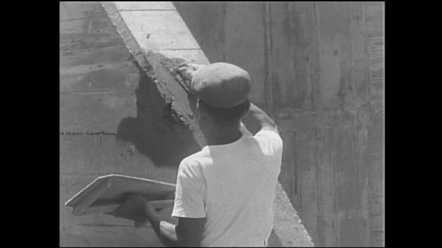 a construction worker spreads mortar on a tide embankment under construction while another hammers. - embankment stock videos and b-roll footage