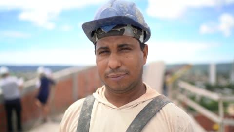 bauarbeiter steht in einer baustelle - stehen stock-videos und b-roll-filmmaterial