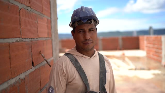 vídeos de stock e filmes b-roll de construction worker standing in a construction site - latino americano