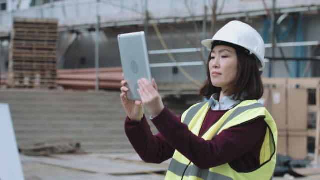 construction worker taking picture with digital tablet of project development - 工事点の映像素材/bロール