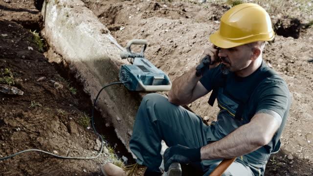 stockvideo's en b-roll-footage met slo mo bouwvakker die op een mobiele telefoon spreekt - werkhelm