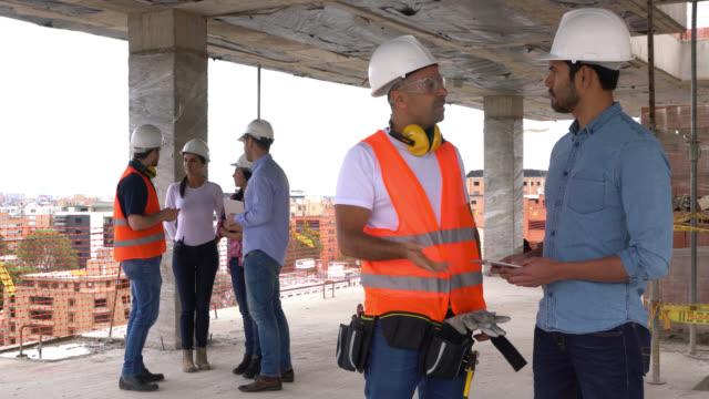 vidéos et rushes de travailleur de la construction de parler avec l'architecte d'un projet et d'autres professionnels à la conversation de fond - vêtements décontractés