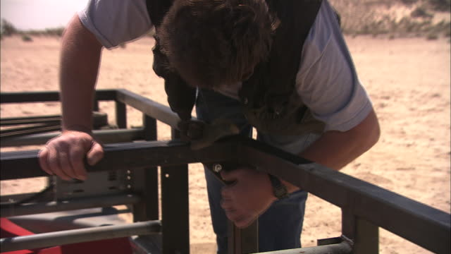 a construction worker tightens a bolt on a steel frame. - bolt stock videos & royalty-free footage