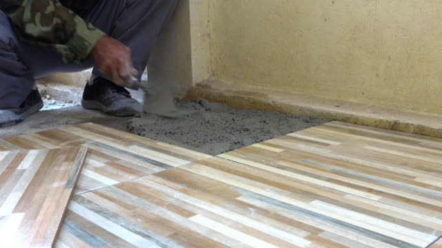 construction worker tiling ceramic tiles floor, dolly shot 4k