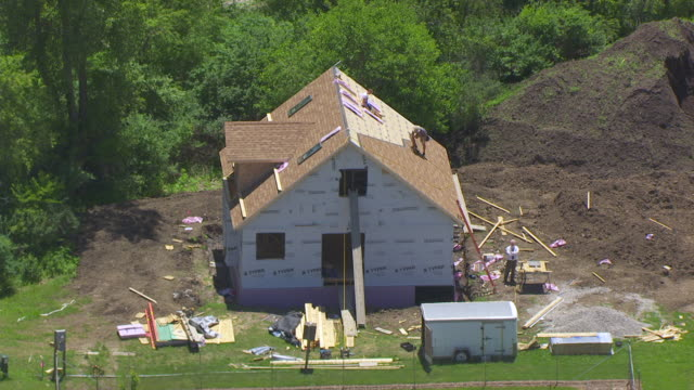 WS AERIAL POV Construction worker tiling on roof / Maharishi Vedic City, Iowa, United States