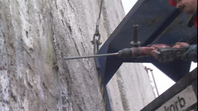 a construction worker uses a concrete drill to make a hole in a wall - drill stock videos & royalty-free footage