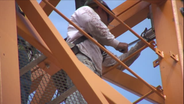 a construction worker uses a tool to tighten a bolt in a girder. - bolt stock videos & royalty-free footage
