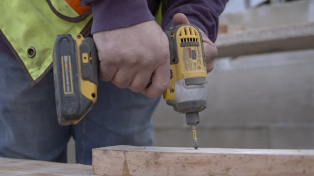 construction worker uses an battery powered impact drill to drive screws in wood forms at a construction site - part of stock videos & royalty-free footage