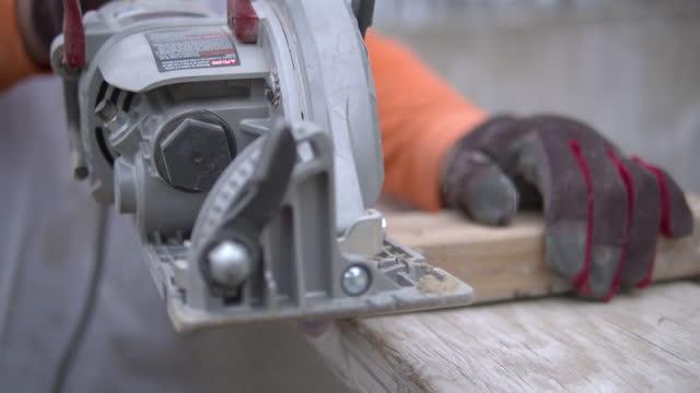 vidéos et rushes de construction worker uses an electric circular saw to cut a 2x4 wood plank at a construction site - bois