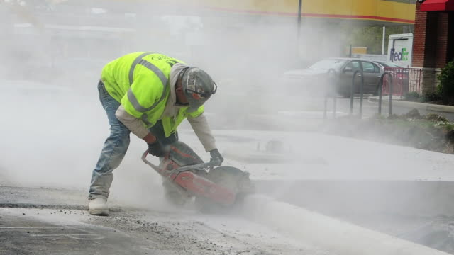 Construction worker uses power saw cuts concrete curb in Westerville Ohio