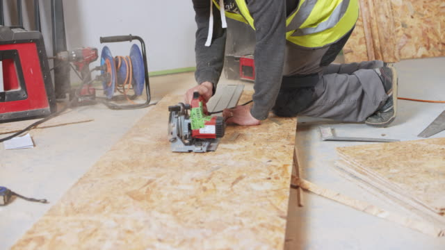 ds construction worker using a metal plank to help him cut the chipboard in a straight line - insulator stock videos & royalty-free footage