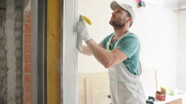 construction worker using a shaving tool to make the edge of the drywall nice and smooth - insulator stock videos & royalty-free footage
