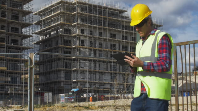 construction worker using digital tablet on site. - surveyor stock videos & royalty-free footage