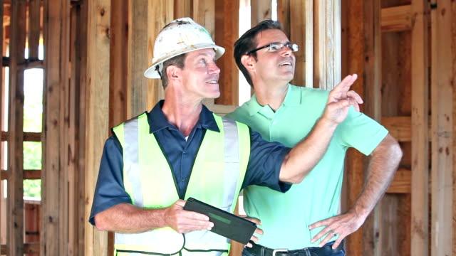 Bauarbeiter mit digital-Tablette, im Gespräch mit Hausbesitzer