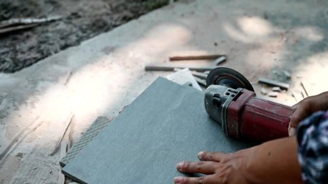 construction worker using electric grinder cutting on ceramic tile - granite rock stock videos & royalty-free footage