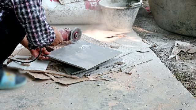 construction worker using electric grinder cutting on ceramic tile - stone material stock videos & royalty-free footage