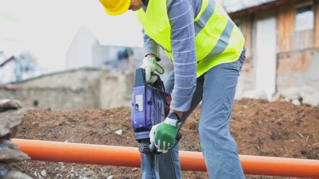 construction worker using jackhammer. working on a construction site. drilling, construction site, construction industry, braking up a rock - pneumatic drill stock videos & royalty-free footage
