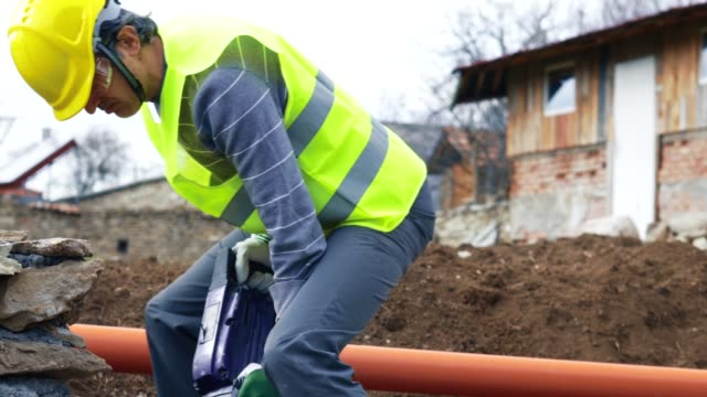 construction worker using jackhammer. working on a construction site. drilling, construction site, construction industry, braking up a rock - road construction stock videos and b-roll footage
