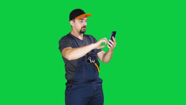 vidéos et rushes de ouvrier de construction utilisant le téléphone intelligent sur l'arrière-plan vert d'écran vert de clé de chroma, le mouvement lent - outil de travail