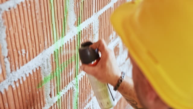 construction worker using spray paint to draw measurements on the wall - wall building feature stock videos & royalty-free footage
