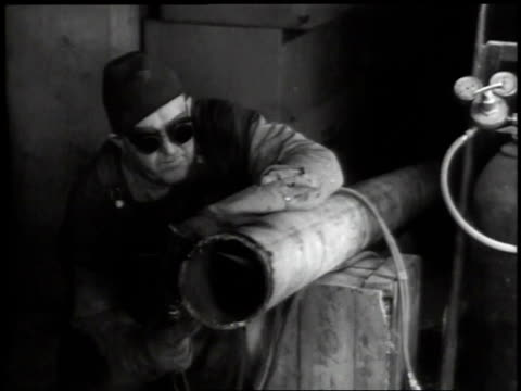 vídeos de stock, filmes e b-roll de 1941 montage construction worker using welding torch to cut a pipe / washington d.c., united states - indústria metalúrgica