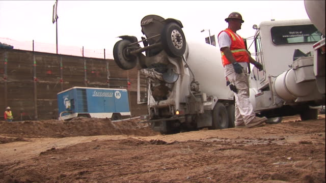 a construction worker waits for a cement mixer to back up. - cement mixer stock videos & royalty-free footage