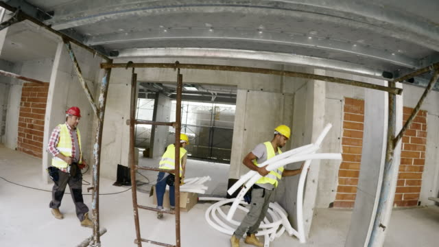 pov construction worker walking at the busy construction site - medium shot stock videos & royalty-free footage