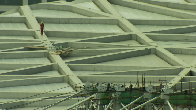 ws ha construction worker walking down roof of beijing national stadium, beijing, china - bird's nest stock videos & royalty-free footage