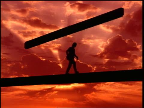 vidéos et rushes de silhouette construction worker walking on steel beam as crane lowers another beam at sunset - un seul homme d'âge moyen
