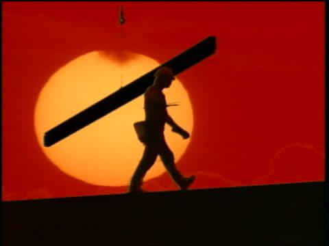 vidéos et rushes de silhouette construction worker walking on steel beam with giant time lapse sunset in background - un seul homme d'âge moyen