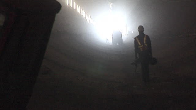 a construction worker walks through the niagara tunnel. - tunnel stock-videos und b-roll-filmmaterial