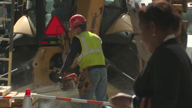 a construction worker watches uses a chain saw to cut through some wood.  the city is busy with cars, and people going by. - road closed sign stock videos & royalty-free footage