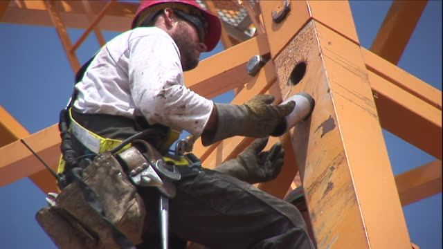 a construction worker wears a safety harness as he installs a large pin high on a tower. - safety harness stock videos & royalty-free footage