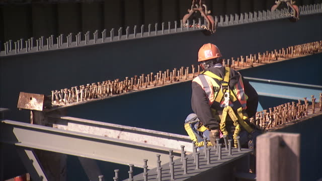 a construction worker wears a safety harness as he moves on girders at a bridge construction site. - safety harness stock videos & royalty-free footage