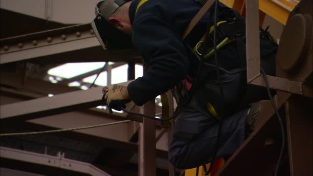 vídeos de stock e filmes b-roll de a construction worker wears a welder's mask as he solders metal. - trabalhador da construção civil