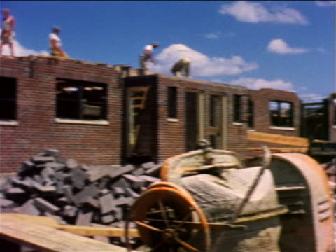 1959 pan construction worker wheeling cement + workers above working on brick structures / phila. - 1950 1959 個影片檔及 b 捲影像
