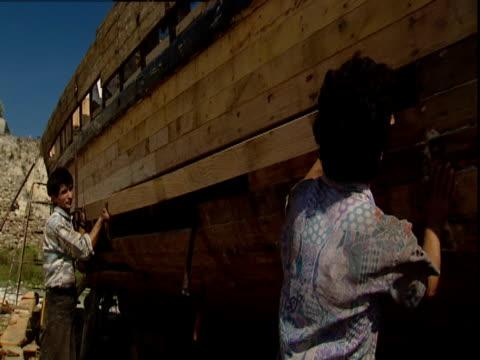 construction workers add lumber to a replica of noah's ark. - avvenimento biblico video stock e b–roll