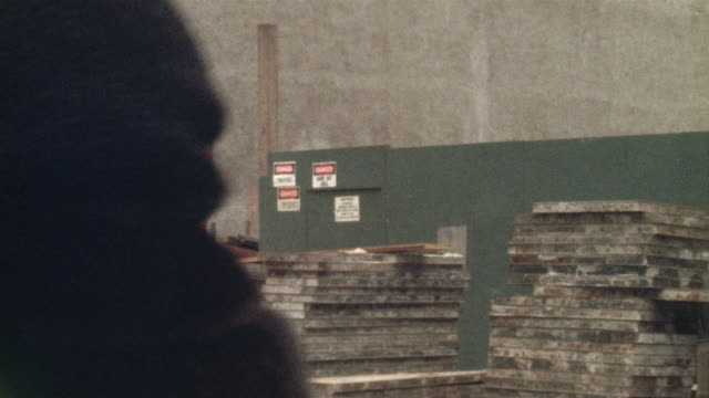 1978 montage ms selective focus pan construction workers and pedestrians walking next to building site fence, new york city, new york state, usa - 1978 stock videos and b-roll footage