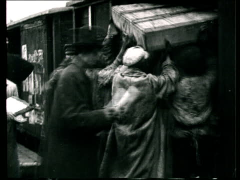 1923 MONTAGE B/W WS PAN Construction workers and soldier on building site of the All-Union Agricultural Exhibition/ MS Men writing on clipboards/ MS Workers unloading crates from freight train/ WS Workers transporting logs/ Moscow, Russia