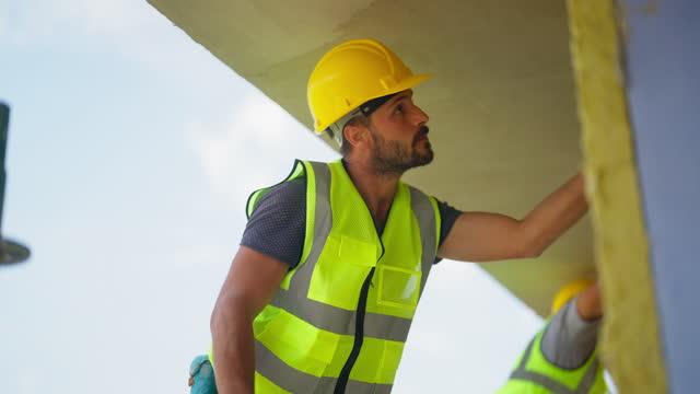vidéos et rushes de ouvriers de la construction appliquant du plâtre sur la façade du bâtiment - ouvrier