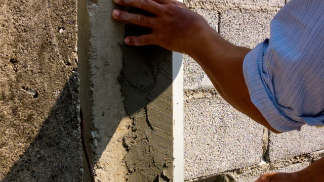Construction workers are plaster pillars and walls